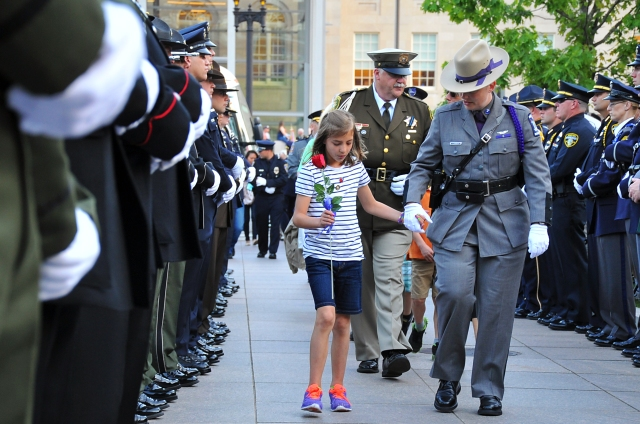 Family members of officers killed in the line of duty are escorted to the survivor's seating area before the National Law Enforcement Officers Memorial candlelight vigil in Washington, D.C., Tuesday, May 9, 2014.  U.S. Coast Guard photo by Petty Officer 2nd Class Patrick Kelley.